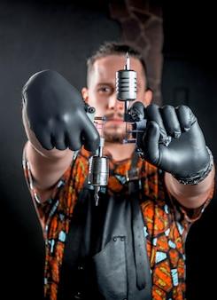 Specialista del tatuaggio che guarda la telecamera nel salone dei tatuaggi