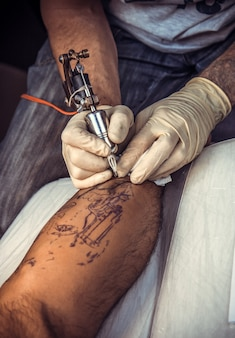 Specialista del tatuaggio che lavora al tatuaggio nello studio del tatuaggio