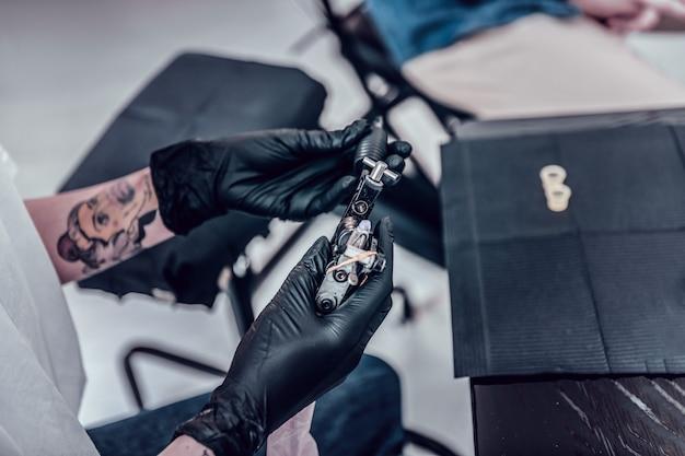 Routine di studio di tatuaggi. maestro del tatuaggio che trasporta la macchinetta con entrambe le mani mentre indossa speciali guanti di gomma nera