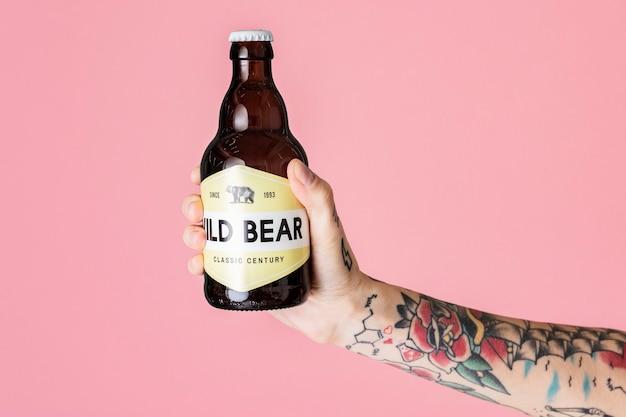 Braccio tatuato che tiene una bottiglia di vetro marrone