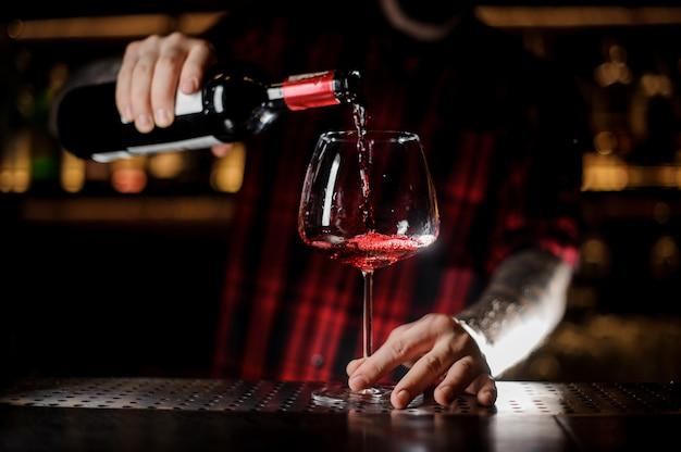 Barista tatuato che versa vino rosso nel bicchiere burgunya