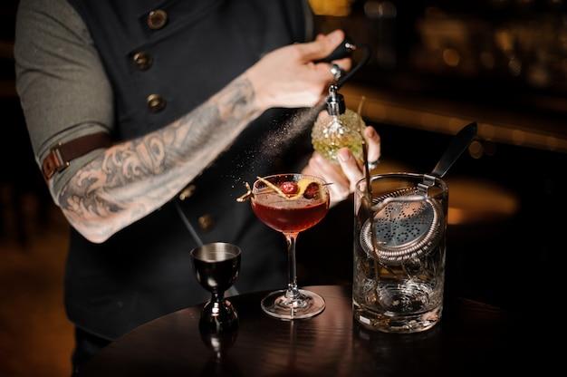 Barista tatuato che spruzza sul delizioso cocktail con un liquido speciale