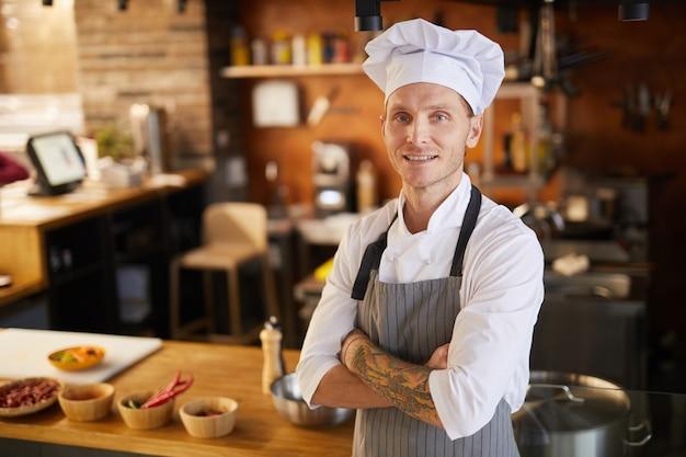 Chef tatuato in posa in cucina