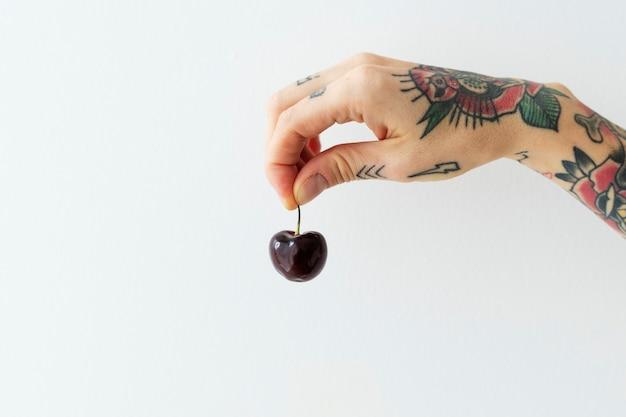 Mano tatuata che tiene una ciliegia fresca