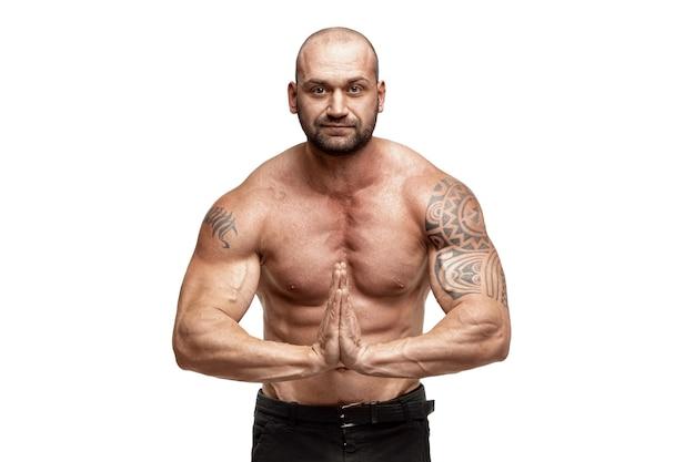 Culturista maschio tatuato che posa sopra la parete bianca. allenamento fitness