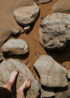 Uomo tatuato in piedi sulle rocce sopra la sabbia