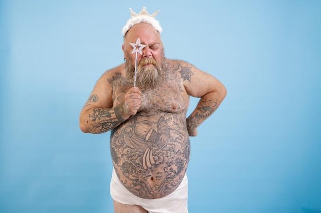 Uomo obeso tatuato con corona guarda attraverso la stella sul bastone magico su sfondo blu
