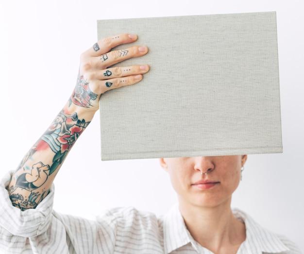 Donna tatuata con in mano un modello di libro
