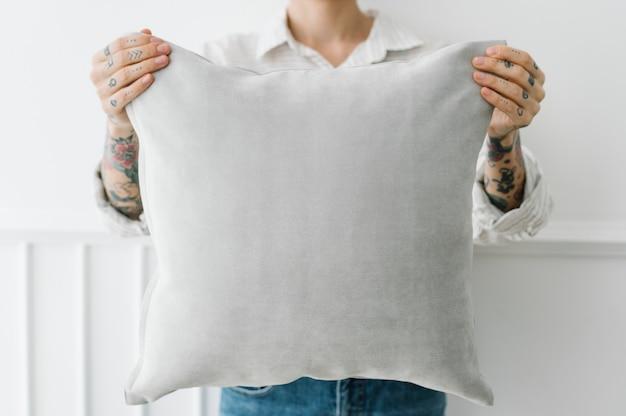 Donna tatuata con in mano un cuscino grigio