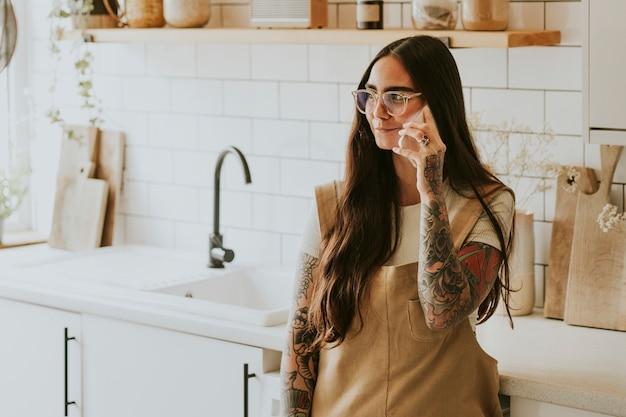 Donna tatuata in cucina che parla al telefono