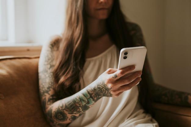 Donna tatuata che usa la sua casa sul divano