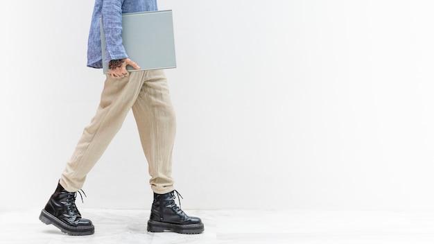 Donna tatuata che cammina con un libro grigio