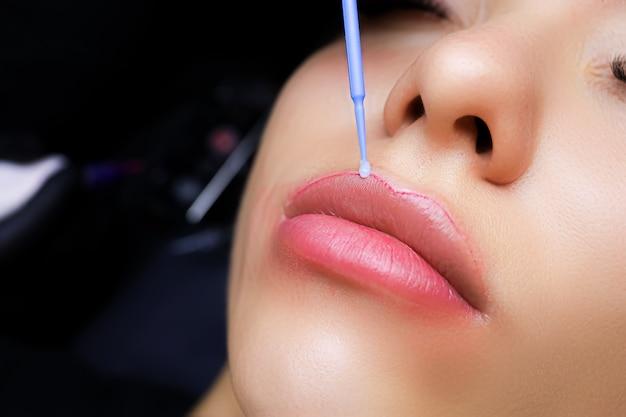 Il tatuatore applica l'anestesia sul contorno delle labbra della modella con un pennellino