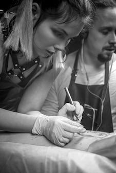 Tattooist lavoro tatuaggio nel negozio di tatuaggi
