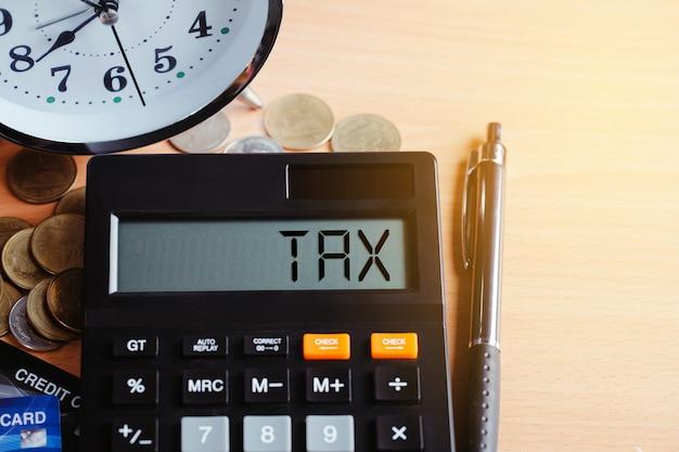 Tasse 2021 concetto di finanza aziendale. calcolatrice con soldi e carta di credito sul tavolo. pagamento delle tasse annuali