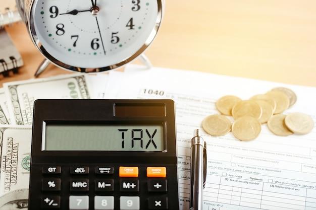 Tasse 2021 concetto di finanza aziendale. calcolatrice con denaro e modulo 1040 sul tavolo pagamento annuale delle tasse