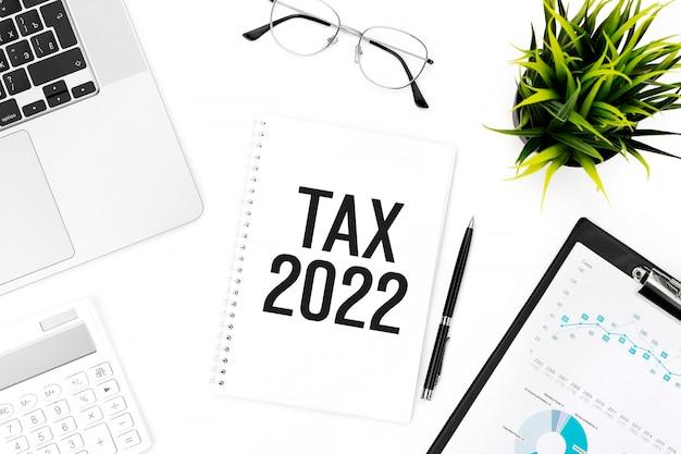 Tasse 2022. blocco note, calcolatrice, grafico, laptop. concetto di contabilità. disposizione piatta.