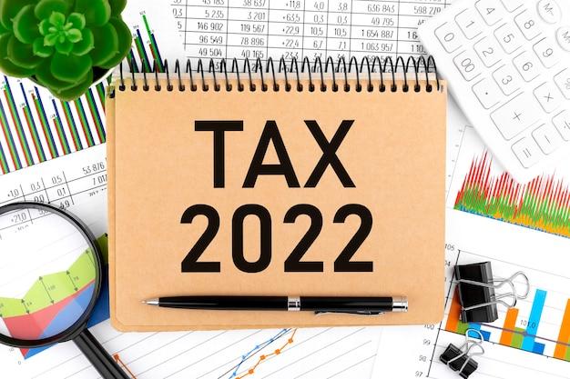 Tasse 2022. blocco note, calcolatrice, grafico, lente d'ingrandimento. concetto di contabilità. disposizione piatta.