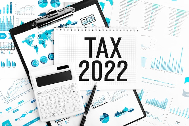 Tasse 2022. taccuino, calcolatrice, grafico. concetto di affari. disposizione piatta.