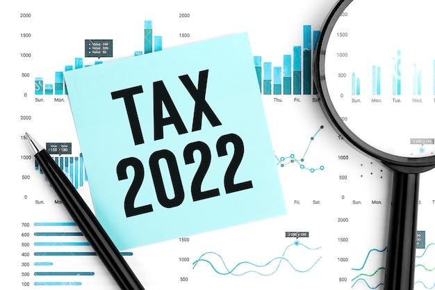 Tasse 2022. adesivo, calcolatrice, grafico. concetto di pianificazione della detrazione fiscale. disposizione piatta.