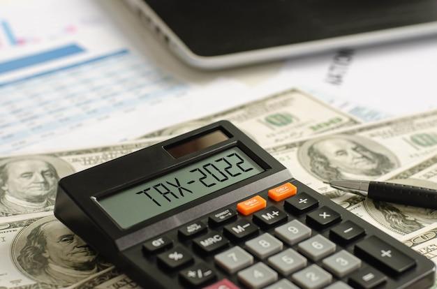 Assistenza fiscale con banconote in dollari sul display del calcolatore 2022 sono scritte assistenza fiscale, detrazioni fiscali.