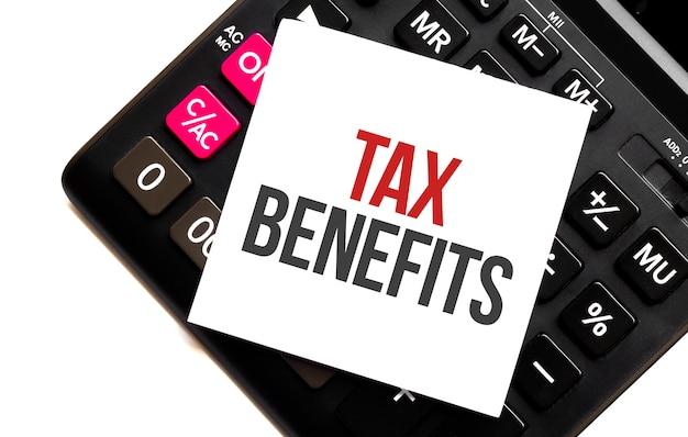 Benefici fiscali testo, scritto su una nota che si trova su una calcolatrice e uno sfondo bianco. posto per il testo