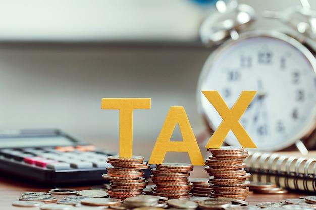 Concetto di imposta. imposta sulla parola messa su monete e calcolatrice, orologio con monete sulle scrivanie. concetto di tempo fiscale