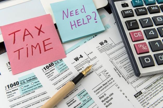 Moduli finanziari fiscali con penna e calcolatrice e adesivo con testo tax time