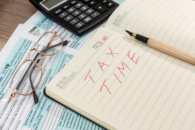 Modulo fiscale 1040 con blocco note e testo tempo fiscale, penna e calcolatrice