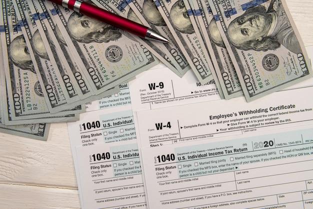 Modulo fiscale 1040 con banconote da 100 dollari statunitensi, concetto di ragioniere economico