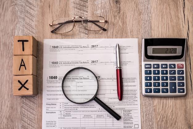 Modulo fiscale con cubi, calcolatrice e lente d'ingrandimento