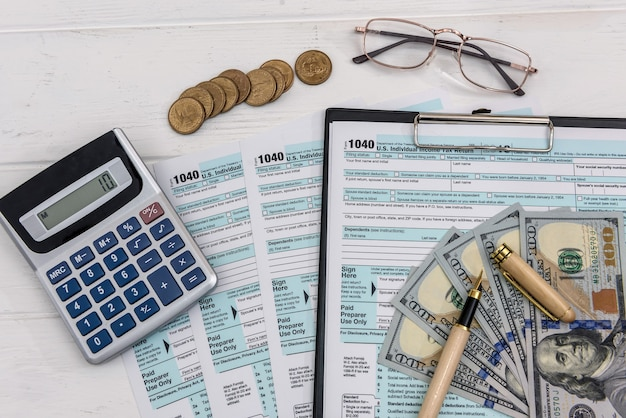 Modulo fiscale con dollari e occhiali e calcolatrice