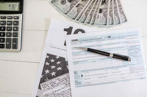 Moduli fiscali 1040 e dollari con penna su fondo in legno