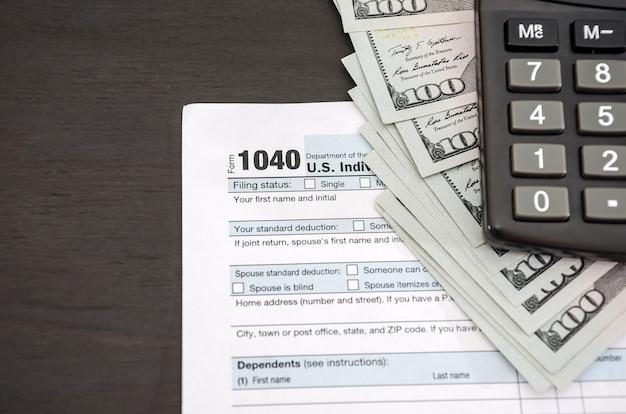 Moduli fiscali 1040 con calcolatrice e dollari su fondo nero