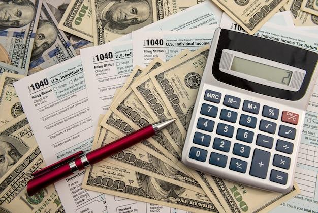 Moduli fiscali 1040 con dollari e calcolatrice per la compilazione in aprile. concetto di tasse.