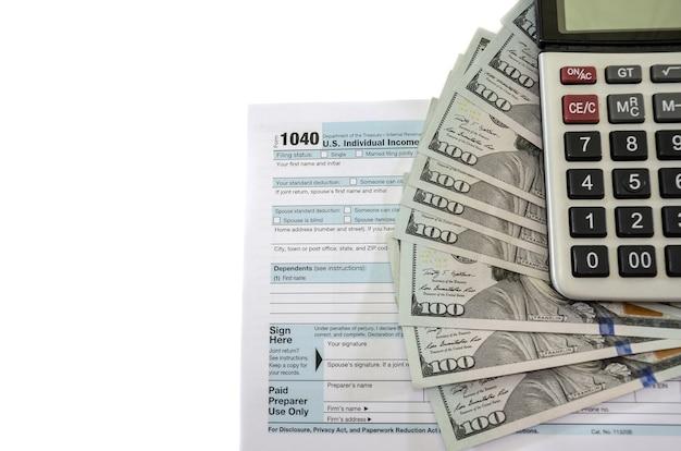 Moduli fiscali 1040 con dollari e calcolatrice su sfondo bianco