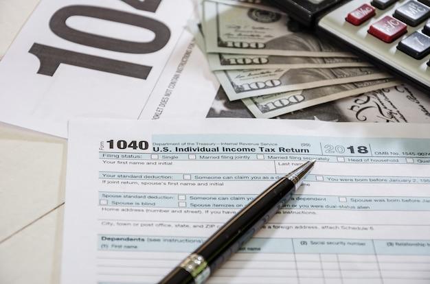 Moduli fiscali 1040 con dollari e penna