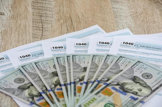 Moduli fiscali 1040 con dollari sul tavolo