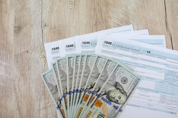Moduli fiscali 1040 con dollari su uno sfondo di legno