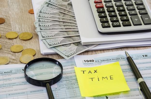 Moduli fiscali 1040 con soldi e calcolatrice sul tavolo