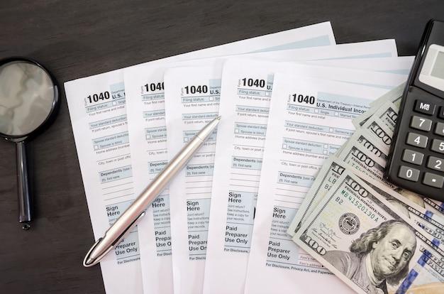 Moduli fiscali 1040 con penna e dollari