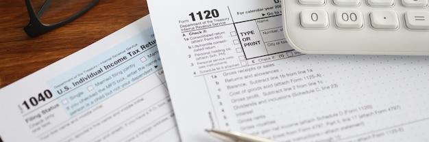 Moduli fiscali con calcolatrice e penna sdraiati sul primo piano del tavolo