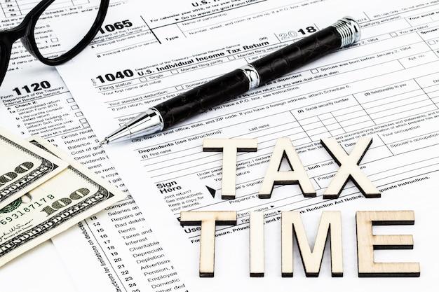I moduli fiscali con gli occhiali, i soldi e la penna. concetto di giorno fiscale.