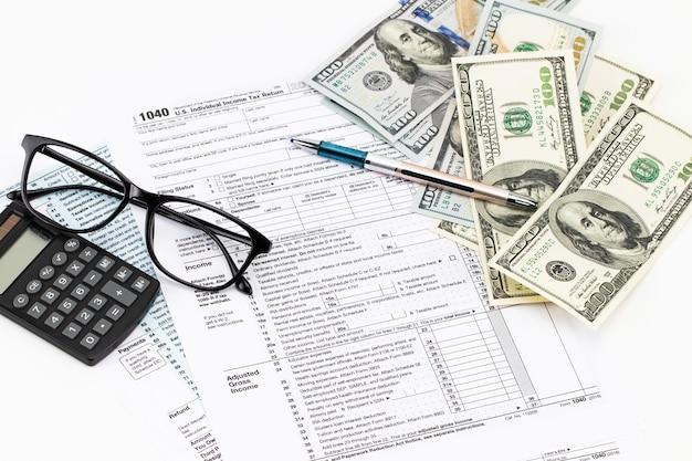 I moduli fiscali con gli occhiali, i soldi e la penna.