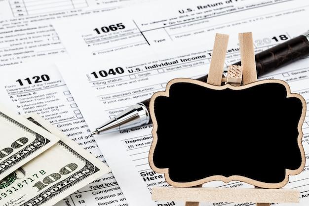 I moduli fiscali con i soldi, la penna e la lavagna con spazio per il testo.
