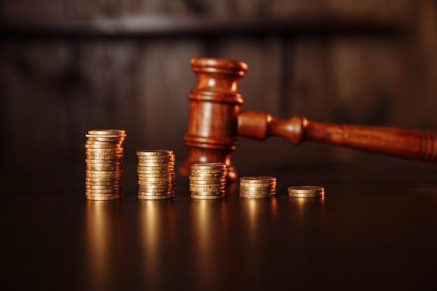 Concetto di pagamento fiscale. pila di monete con martelletto in legno del giudice.