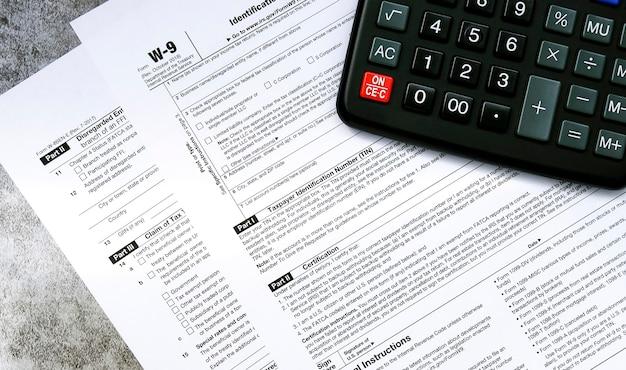Agevolazioni fiscali e moduli fiscali con una calcolatrice per calcolare le tasse su una superficie grigia