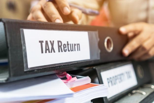 Le cartelle della dichiarazione dei redditi e delle tasse sulla proprietà si accumulano con il raccoglitore nero dell'etichetta sul rapporto di riepilogo dei documenti di scartoffie