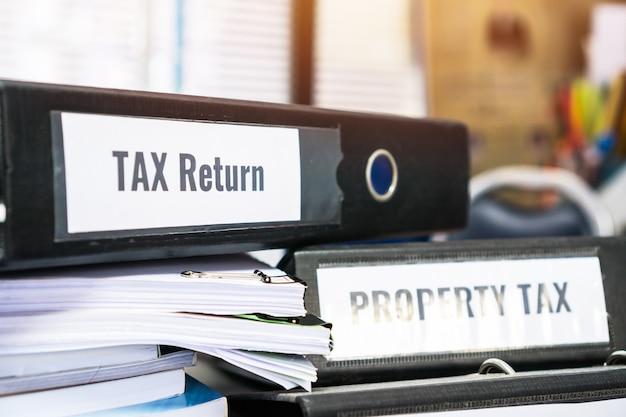 Le cartelle della dichiarazione dei redditi e delle tasse sulla proprietà si accumulano con l'etichetta sul raccoglitore nero