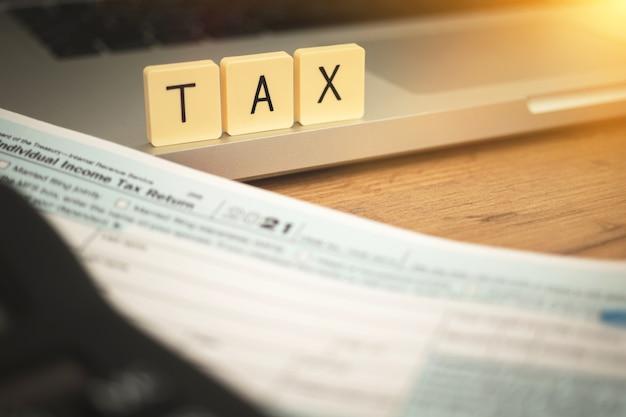 Sfondo del tempo fiscale. parola fiscale su blocchi di legno e modulo di domanda 1040 su business dektop con laptop e calcolatrice